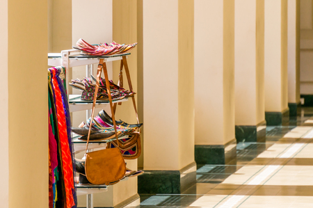 Shelving unit with Indian handcrafted shoes, bags and scarves on sale in a column gallery