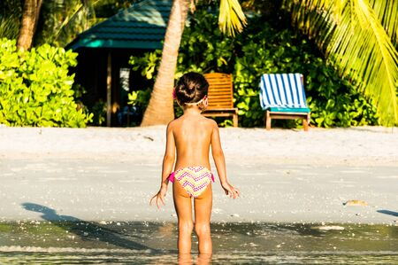 Little girl in greenish water on beach with tropical flora in the Maldives. Back view.