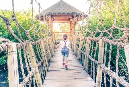 Little girl running away at suspension bridge above water 写真素材