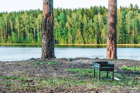 Barbecue grill on the bank of a lake in the forest