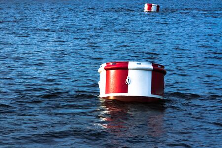 Big round red and white buoys on surface of blue water