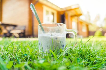 Breakfast of oatmeal porridge in a glass cup standing on green grass near wooden house 版權商用圖片