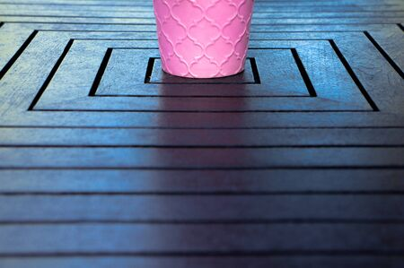 Half of pink ceramic flowerpot standing in middle of wooden table
