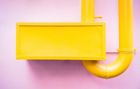 Catchy abstract minimalistic style painted yellow piping on surface of pink pastel colored wall 版權商用圖片