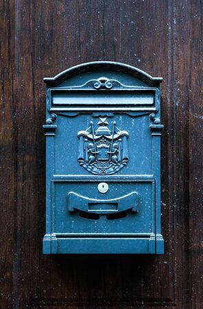 Antique vintage style blue rectangular mailbox hanging on brown wooden door