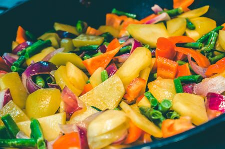 Closeup of stir-fry in wok with different vegetables such as potatoes, bell pepper, green beans, onions.
