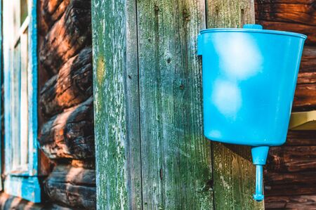 Old blue rural washbasin hanging outdoors on wall of aged and shabby loghouse