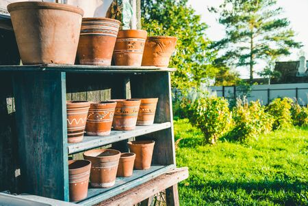 Vintage clay pots with ornamental pattern standing in rows on shelves 版權商用圖片