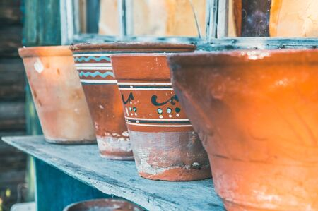 Vintage retro clay pots with ornamental pattern standing outdoors in countryside
