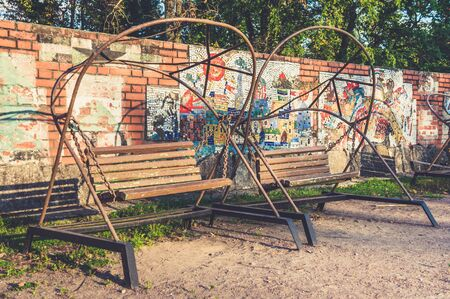 Old retro soviet style wooden bench swings at summer in park near mosaic wall