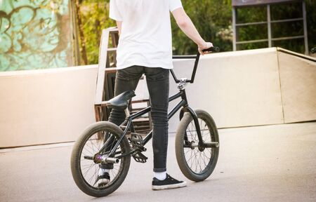 Caucasian teenage boy standing by bmx bike at skatepark