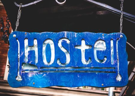 Retro aged blue signboard with inscription hostel in English hanging on chain