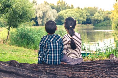 Two children, a boy and a girl, sitting together on a trunk of a tree and watching at lake scenery