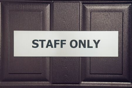 Staff only sign hanging on brown door 版權商用圖片