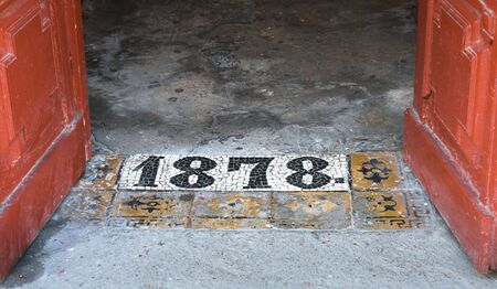 Inscription 1878 on shabby concrete floor by the entrance to an old building in St. Petersbug, Russia