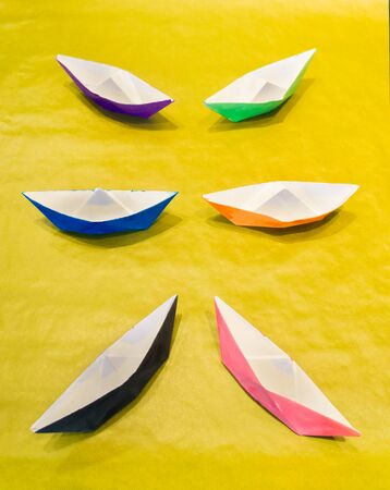 Colorful water color painted paper boats on yellow surface symmetrically arranged
