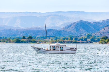 Sail boat on lake Pichola in Udaipur, India. Landscape with colorful hills and mountains.
