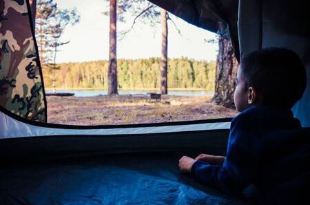 Little boy looking outside camping tent on the lake landscape 版權商用圖片