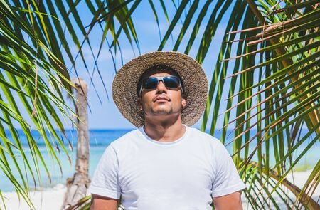 Portrait of young Indian man in sunglasses and straw hat at beach surrounded by palms