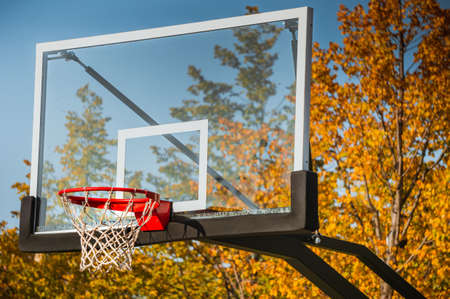 Basketball hoop with net and transparent board in autumn park with blue sky