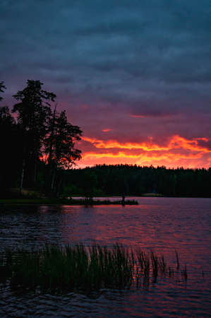 Red sunset with clouds over lake in forest in Russia