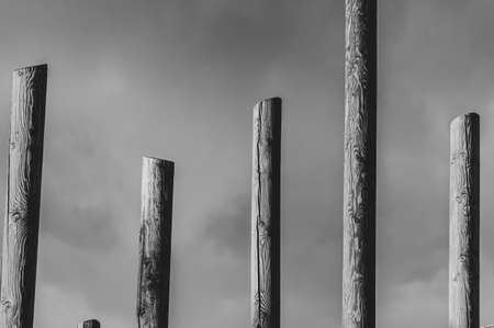 Abstract black and white pillars against cloudy sky