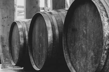 Abstract black and white view of three wooden barrels in row