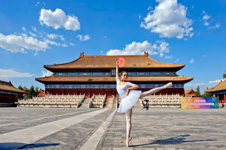 Dancer performing in front of an ancient chinese architectural building Editorial