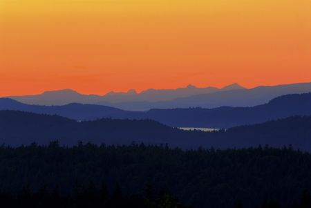 deep orange: Photo transitions from black through blue moutains and hills into a deep orange to bright yellow sky. The viewer can see north along Saltspring Island, the Strait of Georgia, Chemainus, Thetis Island, and the Vancouver Island mountain range. Taken from Je Stock Photo