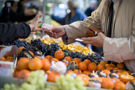 tight focus: A man reaches across a row of fruit in an outdoor market to pay a vendor with a 10 Euro bill. Focus is tight on the bill changing changing hands. The foreground and background are out of focus. Stock Photo