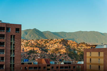 caracas: view of caracas slums at sunset with avila on background with blue sky