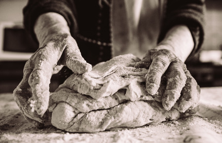 old italian grandma making pasta in the kitchen sepia effect Imagens