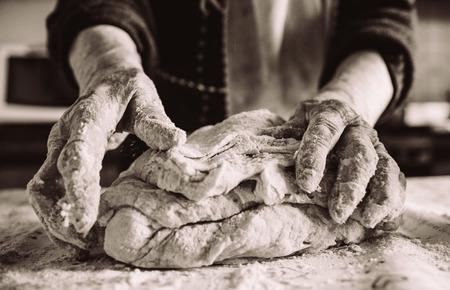 stara włoska babcia robi makaron w kuchni efekt sepii
