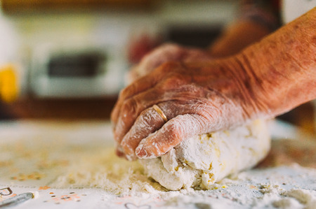 abuela que hace las pastas de la manera tradicional de edad Foto de archivo