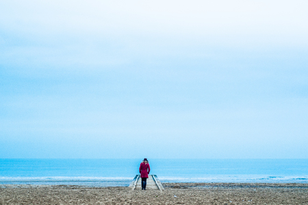 woman walking alone in the beach in winter evening with red dress