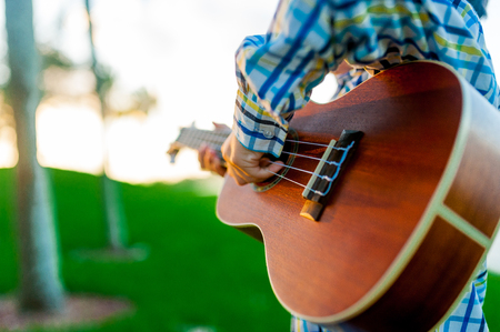 young boy playing acostic wood guitar in park outdoor at sunset