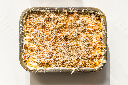 dish of cooked homemade lasagna bolognese on white background