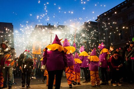 Barcelona, Spain - February 10, 2018: people celebrate traditional catalan correfocs with fireworks and people dressed like demons city center