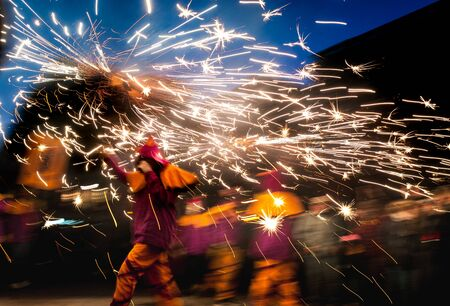 traditional catalan correfocs running in celebration with fireworks and people dressed like demons in barcelona city center, spain Editorial