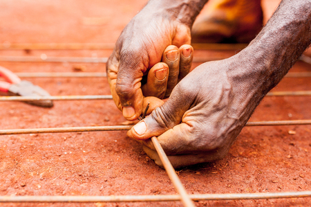 Close up of old African man black hands doing manual work on iron