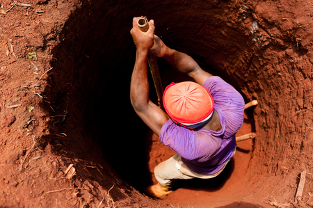 Strong man manually digging well with shovel in African small village with red soil