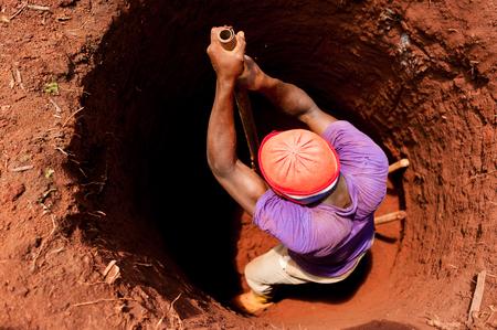 赤い土を持つアフリカの小さな村でシャベルでよく掘る強い男