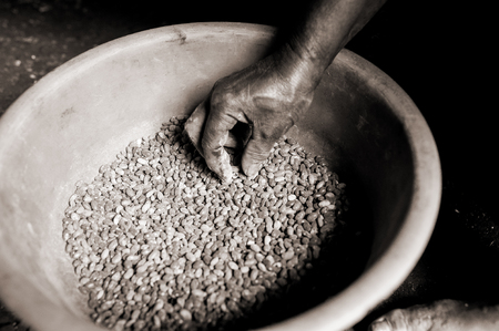 skinny african person hand touching pot of beans in african during difficult famine time in village with sepia effect
