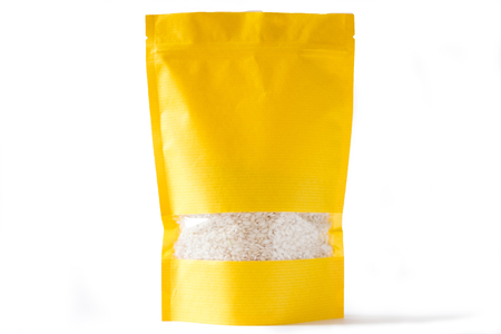 yellow paper doypack stand up bio pouch with window  zipper on white background filled with rice 免版税图像 - 116240604
