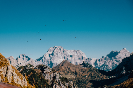 scary view of big majestic rocky dangerous mountains with birds flying over them in autumn