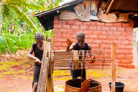 Bafoussam, Cameroon - 06 august 2018:young african girls manually collect the daily water from a water well near their home in the forest Redakční