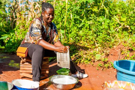 Yaounde, Cameroon - 10 august 2018: young healthy and smiling african woman doing house chores outdoor washing dishes in sunny day