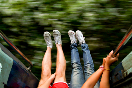 young backpackers couple traveling and living adveture trip exploring asia by train with legs out of fast moving train