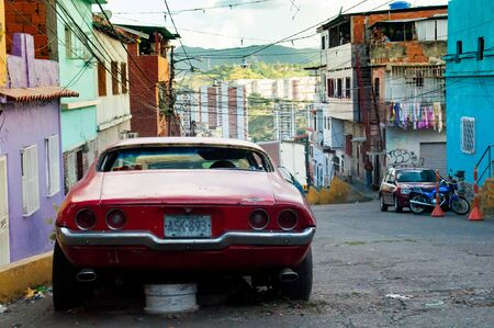 Caracas, Venezuela - 20 june 2018: old american car parked in poor city slum. The country is hit by a severe economic crisis and its not possible to repair cars Sajtókép