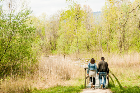 young couple, dressed in modern casual way, walking on wooden pier during sunny day in the woods, immersed in nature Фото со стока